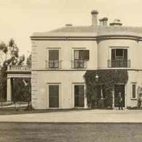 Image: Black and white photograph showing front of large, white two-storey building
