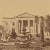 Image: three young girls walk through a garden in front of a two storey stone building with a portico featuring a triangular pediment supported by four columns