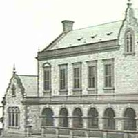 Image: a two storey stone building with a two storey bay window on one elevation, a arched loggia on another side, and ornately curved gable ends.