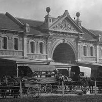 Image: A long two-storey brick terrace building with three large double height arches and decorative gables. Along the street at the front a number of horse drawn carts are parked.