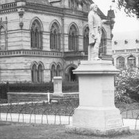 Image: stone sculpture of man in front of building with large stone columns