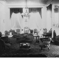 Image: A drawing room of a large house with high ceilings, a fireplace and a number of chairs scattered around the room