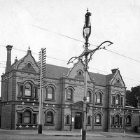 Image: A two-storey brick building with ornate facade is located at the corner of two dirt roads. A lamppost and tram tracks are visible in the foreground