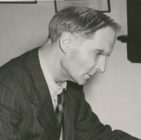Image: A middle-aged, clean-shaven Caucasian man in a 1950s vintage pin-striped suit sits at a desk and writes on a piece of paper. He appears to be deep in thought as he writes