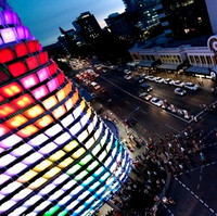 Image: The multimedia screen emits a rainbow of colors over nighttime pedestrians
