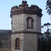 Image: A two-storey octagonal stone tower set within a high wall with a crenellated parapet.