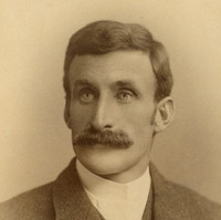 Image: A photographic head-and-shoulders portrait of a young Caucasian man wearing a late-Victorian era suit (without tie). He is sporting a large, luxurious handlebar moustache