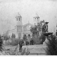 Image: three people standing next to fountain with church in background