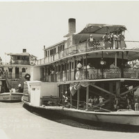 Image: Black and white photograph of two paddlesteamers on a river. Each paddlesteamer has three levels and people are visible standing and sitting on each one. The foremost paddlesteamer is flying the Union Jack flag.