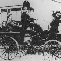 Image: A small group of Caucasian men, women and children dressed in late Victorian attire ride in a carriage-like vehicle along a town road. The vehicle has four spoked wheels and what appears to be an engine. A moustachioed middle-aged man operates it