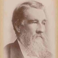 Image: A photographic head-and-shoulders portrait of a middle-aged bearded man in a suit. He has a full head of hair and is looking to the left