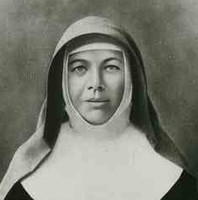 Image: A portrait of a young woman wearing a nun's habit. She is holding a bible and a crucifix