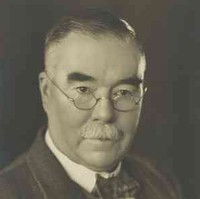 Image: A photographic portrait of a moustachioed middle-aged Caucasian man wearing wire-rimmed spectacles and a mid-20th century suit and tie