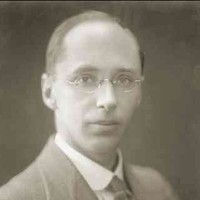 Image: A photographic head-and-shoulders portrait of a young, clean-shaven Caucasian man wearing an early-20th century suit and wire-rimmed spectacles