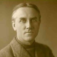Image: A photographic head-and-shoulders portrait of a clean-shaven man wearing a turtleneck sweater and tweed jacket