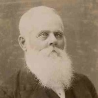 Image: A photographic head-and-shoulders portrait of an elderly man dressed in late-nineteenth century attire and sporting a long white beard