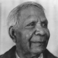 Image: A photographic head-and-shoulders portrait of an elderly Aboriginal man. He is clean-shaven, sporting a short haircut and is wearing a suit jacket and tie
