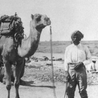 Image: Man in turban standing with saddled camel