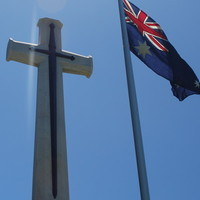 Image: Australian flag in front of cross monument, 2015.