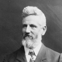 Image: A photographic portrait of a middle-aged Caucasian man with a full beard and head of hair. He is wearing an Edwardian-era suit and tie