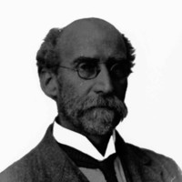 Image: A photographic head-and-shoulders portrait of an elderly Caucasian man wearing an early twentieth-century suit and wire-rimmed spectacles. He is balding, but has a full beard and bushy moustache
