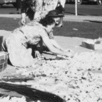 Women arranging flowers on the ground with buildings in the background