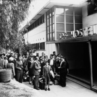 Image: A large group of British migrants of various ages arrive at hostel entrance. A sign above the door reads SPF Hostel.