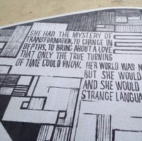 Image: black words on a white surface as part of a poetry/art mural on a wall