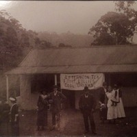 Image: group of people in front of small building displaying banner
