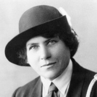 Image: A photographic head-and-shoulders portrait of a young Caucasian woman dressed in an early twentieth century Girl Guides uniform with hat. She has light-coloured eyes and dark hair
