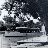 Image: a long, narrow tourist boat with a canvas roof is moored at a concrete dock with a metal railing.