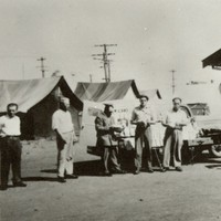 Image: group of men in front of tin huts