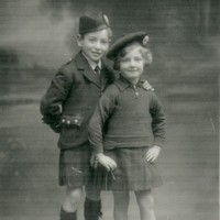 Image: boy and girl in tartan kilts and caps