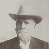 Image: A photographic portrait of an elderly Caucasian man with a white goatee. He is wearing a Stetson hat and a dark-coloured overcoat