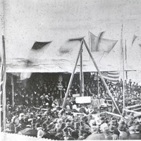Image: a crowd of people in 1870s clothing gather around a small stage where a large foundation stone is being lowered into place.