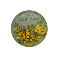 Image: A small circular badge with painted wattle flowers with text above them which says for our own