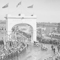 Image: Crowds of people watching cars drive through arch