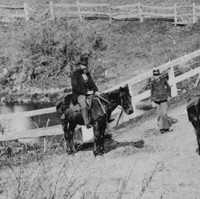 Image: Two bearded Caucasian men dressed in late nineteenth century clothing and stove-pipe hats ride on horseback near a bridge in a remote South Australian setting