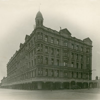 Image: a huge five storey hotel building on the corner of two wide dirt streets. The building has a rounded corner topped with a cupola.