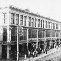 Image: a large three storey building with full height shop windows on the ground and first floors displaying a range of merchandise. A large number of people are walking past on the sidewalk.