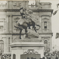 Image: a group of men in dark suits and top hats sit on a stage in front of a statue of a soldier on a horse. A large crowd surrounds them.
