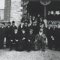 Image: The German consul sitting surrounded by his welcoming party at the front of a house in Hahndorf