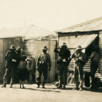 Image: Group of men standing in front of corrugated iron building