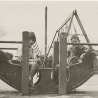 Image: Two boys sit in a 'rocking boat' at a playground. A swings-set is positioned immediately behind the boys