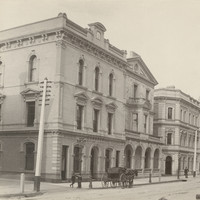 Image: A row of three storey grand stone buildings lining a dirt street.