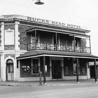 "Image: a two storey corner hotel with a small balcony on one side. A verandah protrudes further out to the street beneath the balcony. A parapet sign reads: ""TISHERS BUCKS' HEAD HOTEL"""