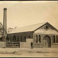 Image: a man in 1870s era clothing stands outside a small stone foundry with arched windows and doors and a medium pitched gable roof. To the left of the building is a fenced yard where more men work at various machinery next to a tall brick chimney.