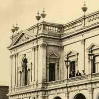 Image: A two storey building with arched windows and an arched porch supporting a balcony. Its parapet is decorated with stone urns and carved pediments.