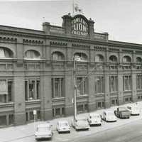 """Image: 1960s cars are parked outside a large, three storey brick factory building. Some of the windows bear striped awnings and there is a parapet sign reading """"Fowlers Lion Factory"""" which is topped with a life-sized lion statue"""