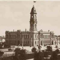 Image: a large two storey stone public building with a tall clock tower protruding from one corner stands on the corner of two city streets. A large park can be seen in the foreground of the image.